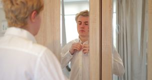 Getting dressed for work. Over the shoulder view of a reflection of a young adult male getting ready for work stock video footage