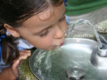 Getting a Drink. Pretty little girl drinking from a water fountain Royalty Free Stock Photography