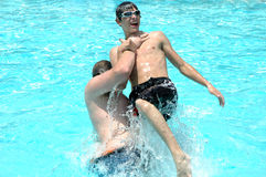 Getting Dunked. Big teenage boy picks smaller teenage boy up and dunks him with a slam into the water Stock Images