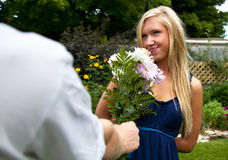 Getting Flowers. A pretty blonde girl smile coyly as she's offered a bouquet of flowers royalty free stock image