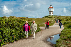 People walking in dunes of Langeoog. People going for a walk in the dunes and getting fresh air on a windy, sunny Sunday afternoon. Location: East Frisian island Stock Photography