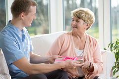 Getting a gift. Old women is getting a gift from a male nurse stock photography