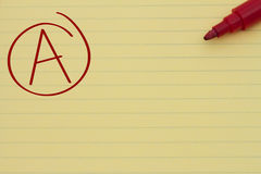 Getting a great grade. Making the grade, Yellow Lined Paper with the grade A in red circled and a marker, Getting a great grade Royalty Free Stock Photo