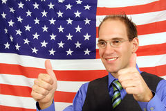 Getting the greencard. A young businessman jubilating in front of the flag of the United States of America Royalty Free Stock Photo