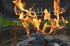 Getting the grill ready for cooking. The flames are ignited. Flames a burst with color as the grill is ignited to begin the barbecue session Stock Photo