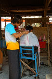 Getting a haircut at the weekly market Stock Image