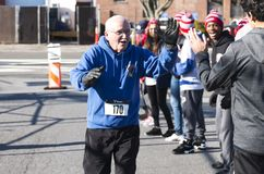 Getting high fives at the end of a road race. West Islip, NY, USA - 24 November 2017: A runner receives high fives from the school track team as he approaches Royalty Free Stock Photography