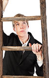 Getting higher. Young blond handsome man climbing wooden ladder stock photos