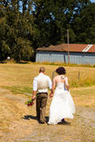 Getting Hitched at a Farm. Bride and groom walk holding hands on their wedding day as they head to the ceremony location Royalty Free Stock Photos