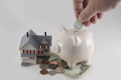 Getting a home loan. A home with money and a piggy bank. A concept of a home loan stock photo