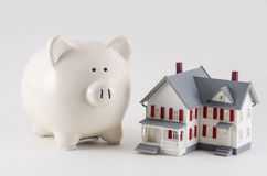 Getting a home loan. A home with money and a piggy bank. A concept of a home loan or saving for a house. Shallow depth of field stock image