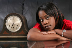 Getting late. Beautiful black woman leaning on a table by an old clock waiting and thinking Stock Image