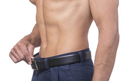 Getting lean. Torso of lean muscular Caucasian man pulling out belt line showing weightloss on white background royalty free stock image