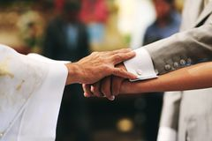 Getting married, hands from bride, groom and priest in a mexican church in mexico city stock photos
