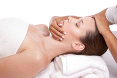 Getting a massage. Beautiful brunette getting a facial massage in a spa center Stock Photography
