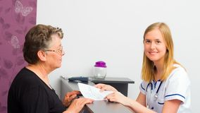 Getting Medical Test Results. Young doctor giving medical test results with explanation to her middle-aged patient royalty free stock photos