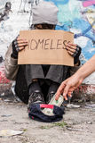 Getting money for food. Kind stranger gives money to homeless man Stock Image