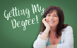 Getting My Degree Written On Green Chalkboard Behind Woman royalty free stock image