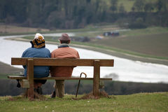 Getting old. Old couple sitting on bench watching the world go by Royalty Free Stock Photo