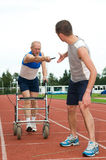 Getting older. Disabled person reaching for an other athlete to pass him the baton. Caricature picture to illustrate helping, giving, disability, ability Royalty Free Stock Image