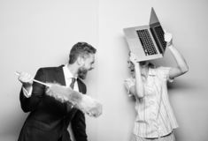 Getting onto a fight. Husband stand with dust brush while wife holding laptop. Couple of handsome man and pretty woman stock photography