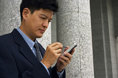 Getting Organized. Asian man in a business suit with a PDA stock photo