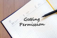 Getting permission write on notebook. Getting permission text concept write on notebook with pen Royalty Free Stock Image