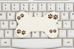 A dog bone with paw prints on a keyboard. Getting pet supplies on the Internet, A close-up of a keyboard with a wood dog bone and paw prints with copy space stock photography