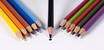 Getting the Point. Eleven color pencils on a white background. One is ahead of the rest and is getting the point royalty free stock image