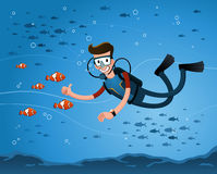 Getting a pose with clown fish. A young man getting a pose with clown fish while diving in the deep sea Stock Photo