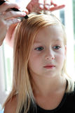 Getting Ready. 5 year old girl patiently sits as her mother begins to braid her hair Royalty Free Stock Image