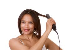 Getting ready. Woman straightening her hair Stock Image