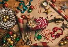 Flat-lay of Christmas decorations and cat in sweater. Getting ready for Christmas or New Year holiday. Flat-lay of decorations, ribbons, gift paper, door wreath stock photography