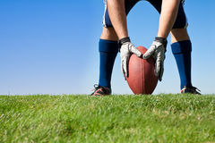 Getting Ready for Football Kickoff. American Football Player sets the ball up ready to kick it off to start the game. Horizontal with lots of Copy Space Stock Photo
