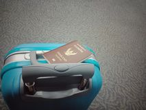Blue luggage with a passport on it stock photography