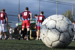 Getting ready for the match. A soccer ball, in focus, in a small stadium with a team of players getting ready for a match Stock Photo