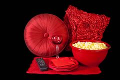 Getting Ready for Movie Night at Home. Comfy pillows, a big bowl of fresh popcorn, a goblet of sparkling refreshment, plates, napkins and the remote control are Royalty Free Stock Photos