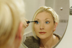 Getting ready for a night out. Woman applying her makeup, in this case her mascara stock photography