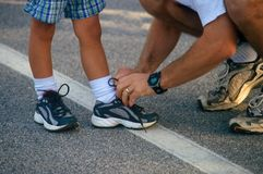 Getting ready for the race. Father helps his son get ready for the upcoming race Stock Photos