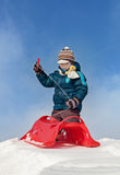 Getting ready for a ride. Boy preparing for a ride with red plastic sleigh on a snowy hill in sunny winter day Royalty Free Stock Images
