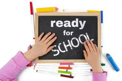 Getting ready for school concept depicted with child hands. Getting ready for school concept depicted with child hands on blackboard with text - top view royalty free stock image
