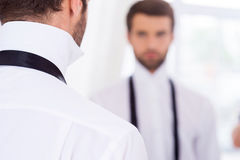 Getting ready for a special day. Rear View of young man in white shirt and untied necktie standing against mirror Stock Images