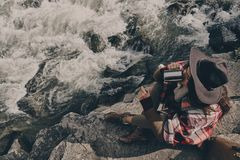 Getting ready to continue the journey. Top view of beautiful young woman covered with blanket drinking hot tee while sitting near the river in mountains Stock Photography