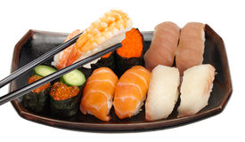 Getting ready to eat. Chopsticks picking up a piece of ebi (shrimp) off a small platter of sushi/sashimi Stock Photos
