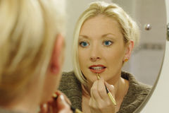 Getting ready to go out. A lady applying her makeup before an evening out royalty free stock photos