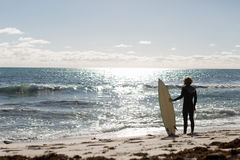 Getting ready to hit waves. A surfer with his surfboard at the beach Royalty Free Stock Images