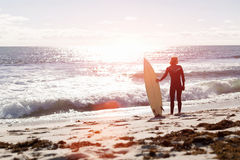 Getting ready to hit waves. A surfer with his surfboard at the beach Stock Photos