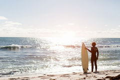 Getting ready to hit waves. A surfer with his surfboard at the beach Royalty Free Stock Photo