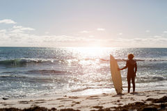 Getting ready to hit waves. A surfer with his surfboard at the beach Stock Photo