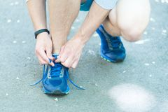 Getting ready to jogging. Hands tying shoelaces sneaker, road background. Hands of sportsman with pedometer tying. Shoelaces sporty sneaker. Running equipment Stock Photos